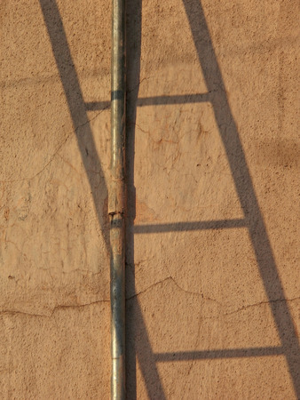 Shadow of a Ladderon a wall with water supplying pipeline photo