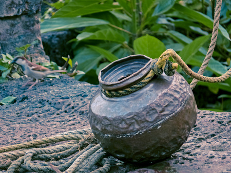 Copper vessel joint to Rahate, a pulley used for drawing water out of a well, India photo