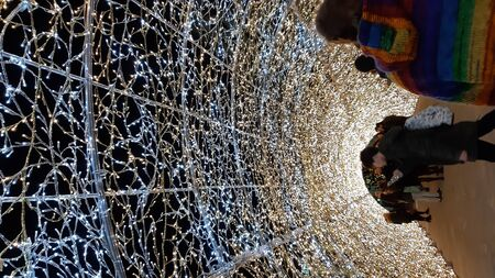 Genoa, Italy - 10122019: An amazing christmas decoration lights on the streets of Genoa in winter with an artistic background and some people enjoing the moment Stock fotó