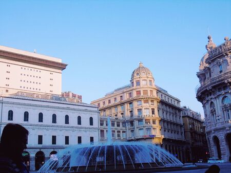 Genoa, Italy - 01222020: Panoramic view to the city center of Genoa in winter beautiful day. Amazing view to the old architecture with blue sky in the background and the moon over the city. 스톡 콘텐츠