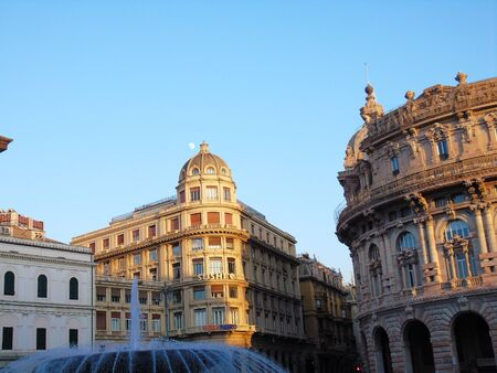 Genoa, Italy - 01/22/2020: Panoramic view to the city center of Genoa in winter beautiful day. Amazing view to the old architecture with blue sky in the background and the moon over the city. 스톡 콘텐츠 - 138473696