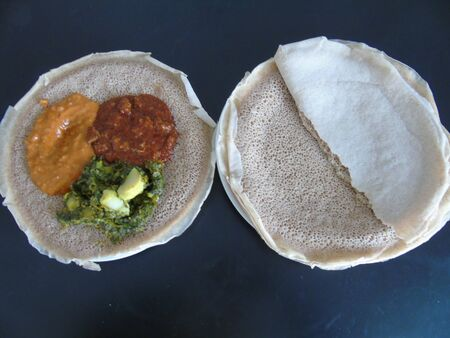Asmara, Eritrea - 08/05/2020: Ethiopian and Eritrean food, assortment of main dishes. Injera is a sourdough flatbread made from teff flour. It is the national dish of Ethiopia, Eritrea. Imagens