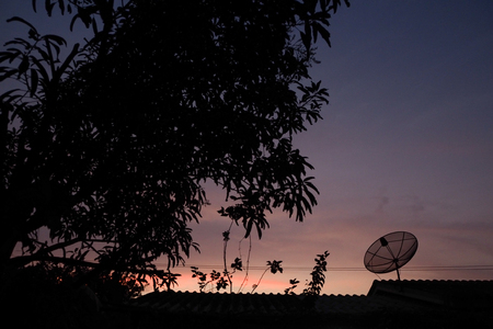 the silhouette of sattlelite on roof in evening blue sky cloud background sunset