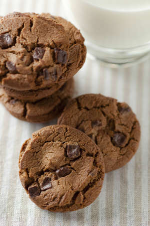 chocolate chip cookies with a glass of milk on the cloth