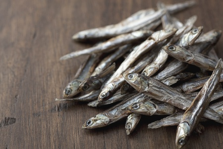 small dried sardines on the old wood board