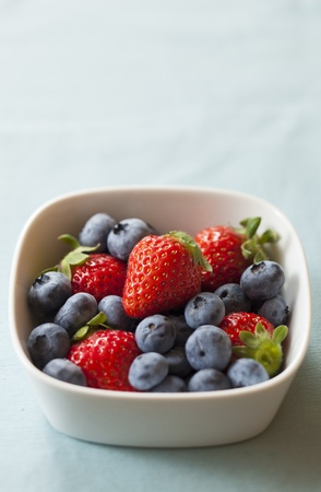 strawberries and blueberries on the light blue cloth