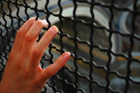girls hand behind bars