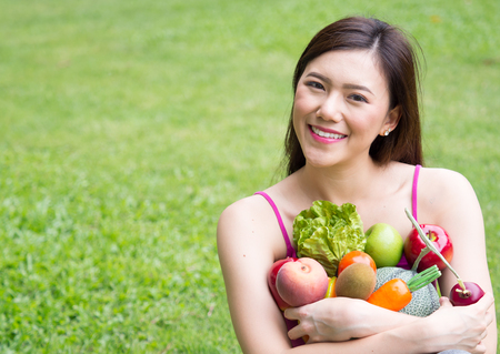 Young beautiful asian woman holding fresh clean food with vegetables and fruits for good healthy over green background, healthy food woman for diet