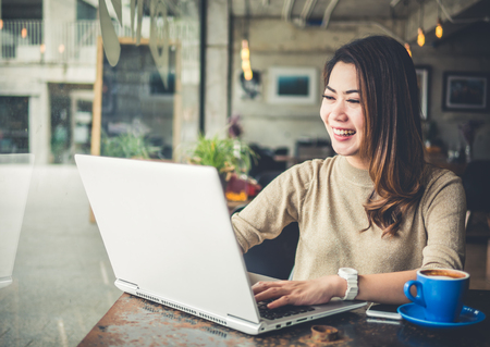 Young beautiful Asian woman working in coffee shop cafe, using computer laptop about business work and online shopping, smile and happy with copy space, vintage tone Фото со стока