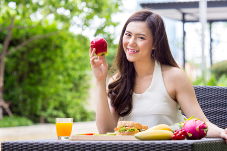 Young beautiful asian woman eating fresh clean food with vegetables red apples fruits for good healthy over green background, healthy food woman for diet