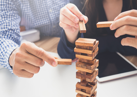 Group of business people building tower by wooden blocks, doing a plan for business strategy, risk, future, teamwork and cooperation concept.