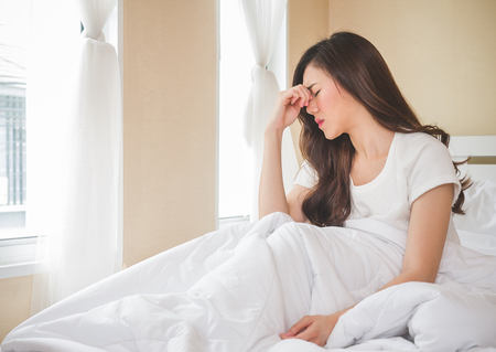Young beautiful asian woman headache on white bed, sad, migraine stressed, crying, disappointed feeling in the morning Stockfoto