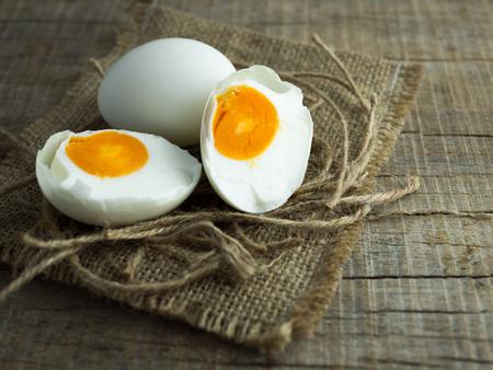 Eendeieren, witte eieren, gezouten eieren met dooier op oude zak en touwen met houten achtergrond. Stockfoto