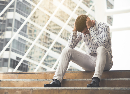 Upset young caucasian businessman tired from work sitting at stairs, unemployment, fired from job, disappointed, loss and feeling down concept Stock Photo