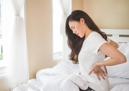 Young woman having back ache sitting on white bed.