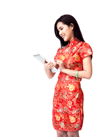 Chinese new year woman concept, isolated asian woman wearing red dress Cheongsam holding tablet