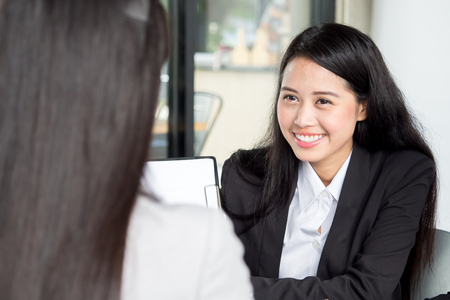 telephone interview: Young asian businesswoman in modern office, discussing with colleague during meeting