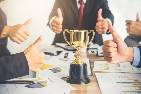 Businessman show thumbs up with trophy, reward, winner, champion and successful for business 写真素材
