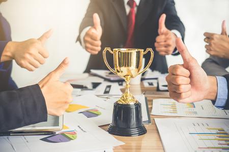 Homme d'affaires montre pouce en l'air avec trophée, récompense, gagnant, champion et réussi pour les affaires Banque d'images