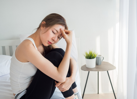 Young beautiful asian woman headache on white bed, sad, stressed, crying, disappointed feeling in the morning