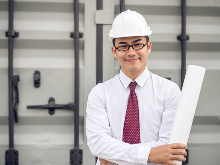 Portrait of young man asian engineer, holding drawing/blueprint at factory