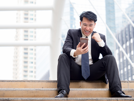 아시아 사업가 행복 스마트 전화를 사용하는 동안  성공적인 사업에 대 한 좋은 뉴스를받는 휴대 전화