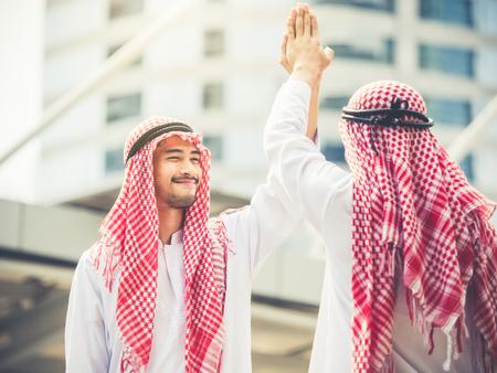 Greeting of arab businessman in the modern city, successful, happy, good feeling, winner, hi five acting Stock Photo
