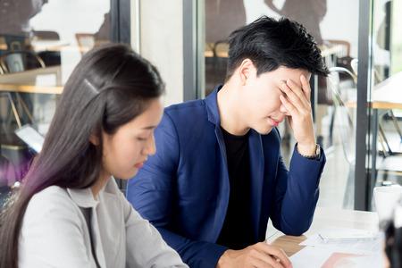 怒り狂ったアジア ビジネスの男性と女性動揺感、カフェ オフィスでの悪いニュースを知って、会議中に失望を強調