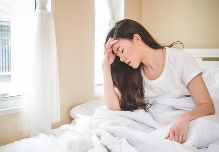 흰색 침대, 슬픈, 편두통에 젊은 아름 다운 아시아 여자 두통 강조, 울고, 아침에 실망 된 느낌 스톡 콘텐츠