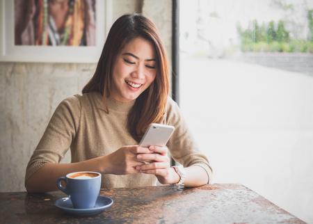 Mulher bonita asiática nova que usa o telefone esperto para o negócio, compra em linha, dinheiro de transferência, financeiro, Internet banking. no café café sobre fundo desfocado.