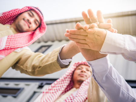 De ingenieur  de architect, Arabische zakenman die handen stapelt drukt hun groepswerk en samenwerking uit