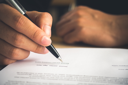 hand of businessman writing on contractbooknotebook, signing a signature for business agreement.