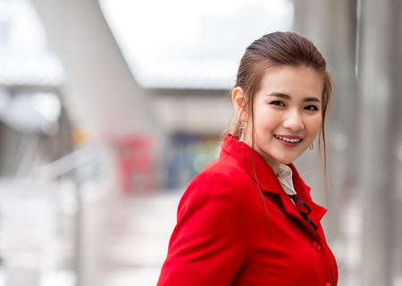 Portrait young asian woman in red suit, flight attendantair hostage in airport