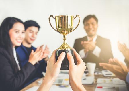 Zakenman duimen opdagen met trofee, beloning, winnaar, kampioen en succesvol voor het bedrijfsleven