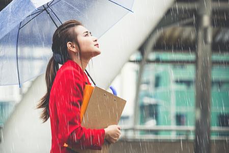 Joven empresaria asiática con documentos de negocios y paraguas caminando bajo la lluvia en la ciudad