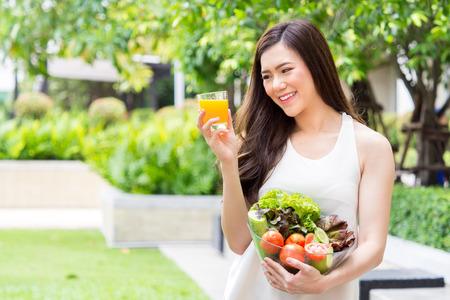 신선한 깨끗한 음식을 야채  오렌지 주스와 녹색 배경, 건강한 음식을 통해 좋은 많은 과일을 먹는 젊은 아름다운 아시아 여자 다이어트