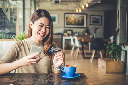 Young beautiful asian woman using smart phone and credit card for shopping online in coffee shop cafe, vintage tone color Фото со стока