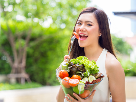 Young beautiful asian woman eating fresh clean food with tomato vegetables and fruits for good healthy over green background, healthy food woman for diet 스톡 콘텐츠