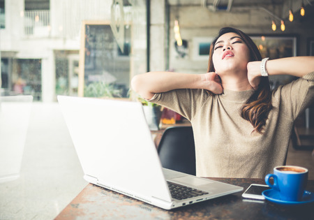Young beautiful asian woman feeling hurt,fatigue, pain at neck, muscle during working with laptop in coffee shop cafe, stretching arms and body for relaxing, vintage tone, office syndrome concept Archivio Fotografico
