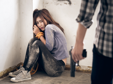 A murdererterroristprisoner man holding gun kidnapping young woman for a hostagerapeintimidate, violencerobberykiller concept. Imagens