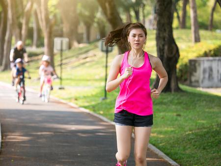 Het openluchtconcept van de vrouwengeschiktheid, het jonge Aziatische mooie vrouw  sportmeisje lopen lopen bij openluchtpark met vers, ontspant, gelukkig gevoel.
