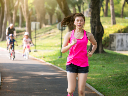 Woman fitness outdoor concept, young asian beautiful womansport girl running walking at outdoor park with fresh, relax, happy feeling.