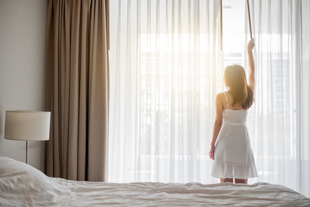 Mujer asiática despierta feliz por la mañana, abriendo las cortinas sobre la ventana blanca, sintiéndose relajado y fresco