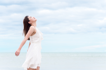 Asian beautiful woman breathing up for fresh air feel relaxing and happy over seabeach and sky background