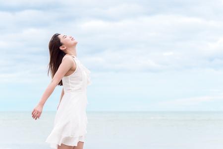 De Aziatische mooie vrouw die voor verse lucht ademen voelt ontspannend en gelukkig over overzees  strand en hemelachtergrond