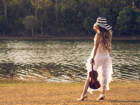 acoustics: Young woman musicianviolinist on white dress holding violin over riverparkforest, freedom lifestyle music vintage tone concept. Stock Photo