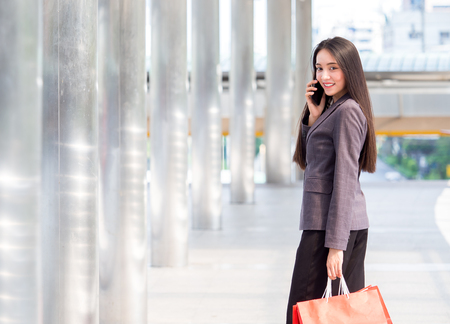 Close up woman holding shopping bag with colorful walking in the city with copy space