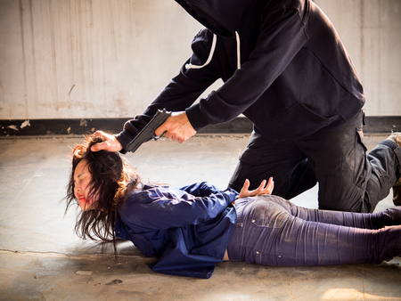 A murdererterroristprisoner man holding gun kidnapping young woman for a hostagerapeintimidate, violencerobberykiller concept. Stock Photo