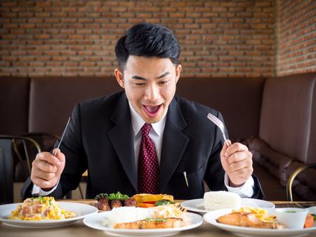 Jonge Aziatische zakenman in formeel kostuum die hongerig voelen, etend veel voedsel op lijst bij koffie Stockfoto