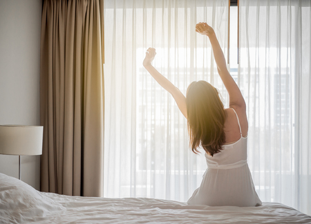 Asian woman wake up in the morning, sitting on white bed and stretching, feeling happy and fresh Stockfoto